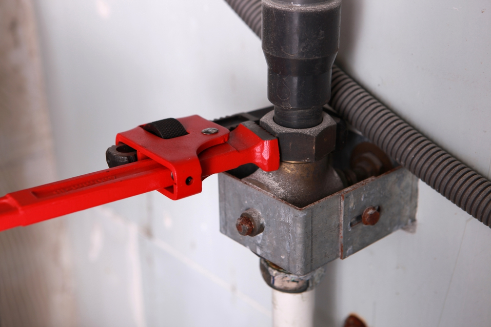 A red wrench attached to a pipe