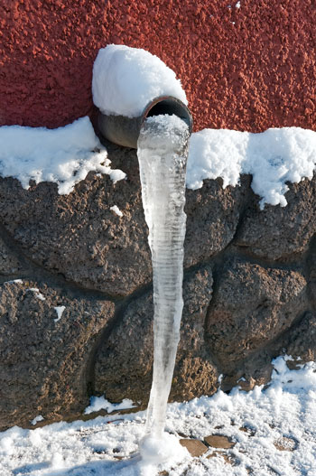 An icicle hangs from an outdoor pipe.