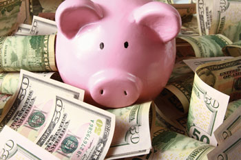 A pink piggy bank surrounded by money is seen.