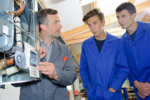 Two young students are being taught in a plumbing apprenticeship
