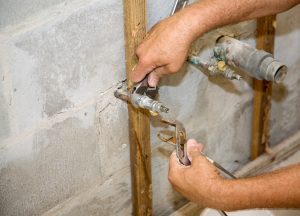 Plumbers hands using a wrench and pliers to loosen a pipe.