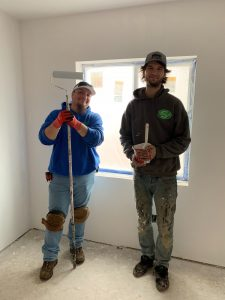 Simpson Plumbing employees volunteering and painting a room.
