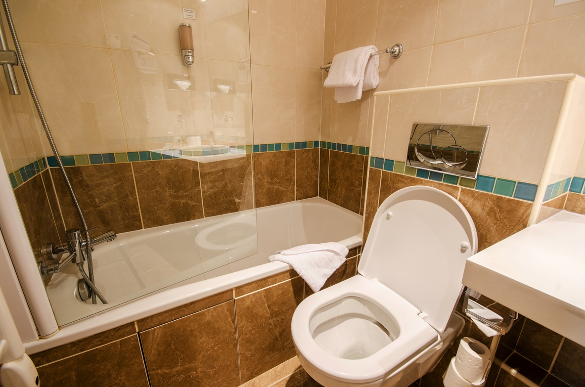 A toilet and tub in a modern bathroom.