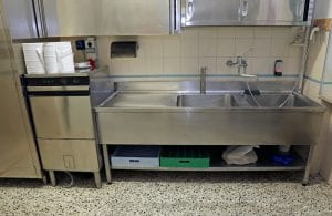 The sink in a commercial kitchen is seen.