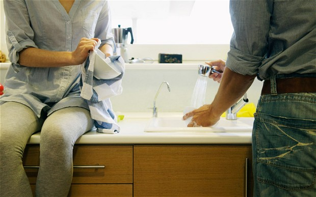 Man and Woman doing the Dishes with clogged garbage disposal that's been fixed